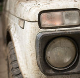 Muddy White Jeep and Headlight Stock Photography