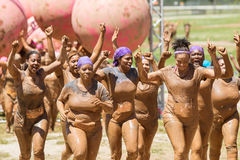 Muddy Women Celebrate As They Finish Dirty Girl Mud Run. Hampton, GA, USA - April 23, 2016: A group of muddy women celebrate with raised arms as they jog toward royalty free stock photo