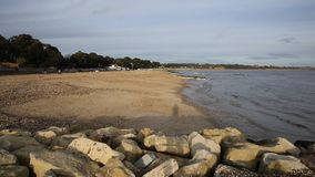 Mudeford beach Christchurch Dorset England UK PAN. Mudeford near Christchurch Dorset England UK with rocks in foreground stock video