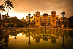 Mudejar Pavilion and pond at sunset. Sevilla. Placed in the Plaza de America, houses the Museum of Arts and Traditions of Sevilla, Spain. Built in 1928 for the Stock Photography