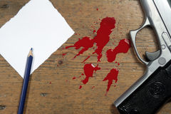 Muder Scene. Hand gun and blood splatter, on wooden floor with pencil and paper.Murder Scene or suicide note Stock Image