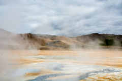 Mudpot in the Namafjall geothermal area, Iceland - area around boiling mud is multicolored and cracked Royalty Free Stock Photos