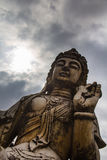 Mudra under a cloudy sky. Statue oblique representing a lotus position and mudra with cloudy sky royalty free stock photos