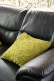 Muebles de cuero negros del sofá con la almohada verde Fotografía de archivo libre de regalías