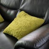 Muebles de cuero negros del sofá con la almohada verde Fotos de archivo libres de regalías
