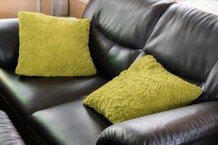 Muebles de cuero negros del sofá con la almohada verde Foto de archivo