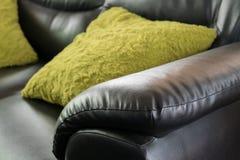 Muebles de cuero negros del sofá con la almohada verde Fotografía de archivo