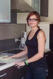 Muebles de la limpieza de la chica joven en la cocina Imágenes de archivo libres de regalías