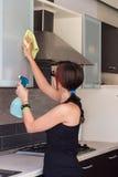Muebles de la limpieza de la chica joven en la cocina Foto de archivo