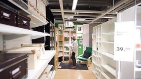 Muebles de las compras de la mujer en biblioteca moderna de la compra de la tienda de Ikea almacen de metraje de vídeo