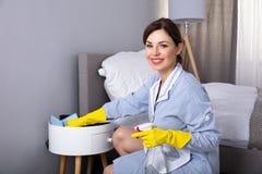 Muebles de limpieza de la criada con el plumero fotografía de archivo