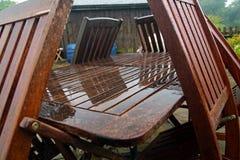 Muebles del jardín en un día de verano decepcionante mojado imagen de archivo