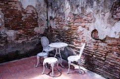 Muebles del jardín fijados con la pared de ladrillo vieja Foto de archivo libre de regalías