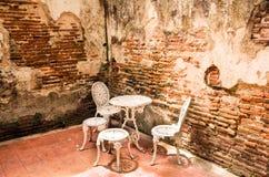 Muebles del jardín fijados con la pared de ladrillo vieja Fotos de archivo