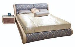 Muebles modernos beige grises de lujo de la cama con las ropas de cama modeladas con el cabecero floral de la textura de la tapic fotos de archivo libres de regalías
