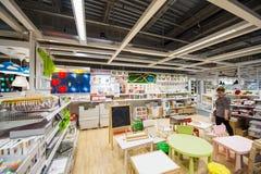 Muebles y juguetes de compra de la mujer para el sitio de los niños Foto de archivo libre de regalías