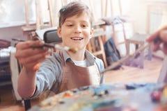 Mueca adolescente emocionada extensamente mientras que mezcla las pinturas Foto de archivo
