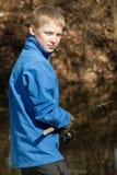 Mueca del pescador adolescente en la charca con la barra Imagen de archivo libre de regalías