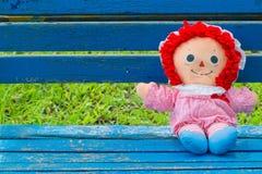 Muñeca linda de la muchacha que se sienta en un banco del vintage Foto de archivo libre de regalías