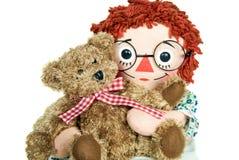 Muñeca que abraza el oso de peluche Imagen de archivo libre de regalías