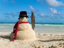 Muñeco de nieve de la Navidad en la playa Fotos de archivo libres de regalías