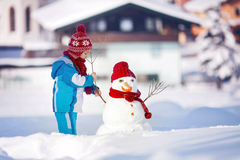 Muñeco de nieve feliz del edificio del niño hermoso en el jardín, invierno Fotos de archivo libres de regalías