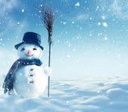 Muñeco de nieve que se coloca en paisaje de la Navidad del invierno Imagen de archivo