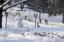 Muñeco de nieve y conducción de niños en el parque Fotos de archivo libres de regalías