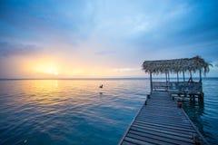 Muelle con un tejado del palapa durante puesta del sol y el agua azul tranquila fotografía de archivo