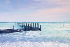 Muelle de madera abandonado en el mar dentro de la salida del sol El color rosado azul apacible del cielo, falta de definición ag Fotografía de archivo libre de regalías