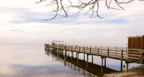Muelle de madera con los pájaros durante la estación del invierno Foto de archivo