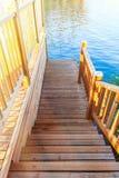 Muelle de madera del río Pendiente al agua en los rayos del sol poniente Fotografía de archivo libre de regalías