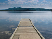 Muelle de madera en un lago tranquilo hermoso Canadá yukon Imagen de archivo libre de regalías