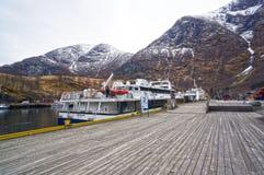 Muelle de madera y los barcos de cruceros en los fiordos y las montañas noruegos Foto de archivo libre de regalías