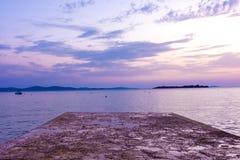 Muelle de piedra hermoso en el Landscap adriático de Croacia de la puesta del sol del océano Foto de archivo libre de regalías