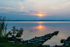 Muelle de piedra romántico, calzada en un lago en una puesta del sol, Uveldy, los Urales, Rusia Foto de archivo libre de regalías