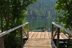 Muelle del barco en un lago en el bosque Imágenes de archivo libres de regalías