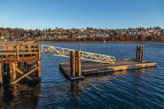 Muelle del bote pequeño del embarcadero blanco de la roca con la ciudad detrás Imagen de archivo libre de regalías