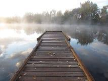 Muelle en el lago brumoso de la mañana Imagenes de archivo