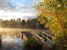 Muelle en el lago de niebla de la salida del sol Foto de archivo