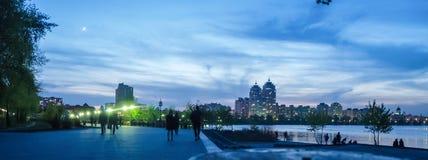 Muelle hermoso de la ciudad en el crepúsculo del verano Gente que camina por la tarde Iluminación azul fotografía de archivo