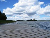 Muelle Pier Catwalk en el lago con las nubes en el cielo en fondo imagen de archivo libre de regalías