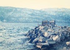 Muelle y rocas en el lago en invierno Foto de archivo libre de regalías