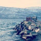 Muelle y rocas en el lago en invierno Imagen de archivo