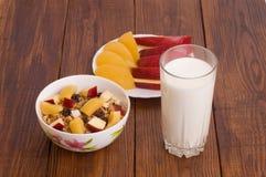 Muesli用桃子、苹果和一杯牛奶 免版税图库摄影