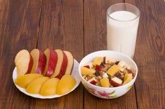 Muesli用桃子、苹果和一杯牛奶 库存照片