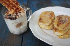 Muesli用酸奶和奶蛋烘饼在一玻璃杯,法式多士用桂香 库存图片