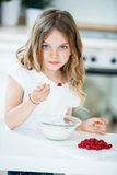 Muesli еды маленькой девочки с полениками Стоковое Фото