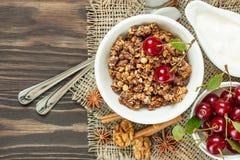 Muesli с соусом вишни и для завтрака на деревянном backgroun Стоковые Фотографии RF