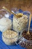 Muesli, хлопья для завтрака, хлопья и рис в стеклянной таре на деревянном столе еда деревенская Стоковое фото RF